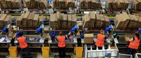 Trabajadores en la zona de preparacion de pedidos de un almacen de Amazon